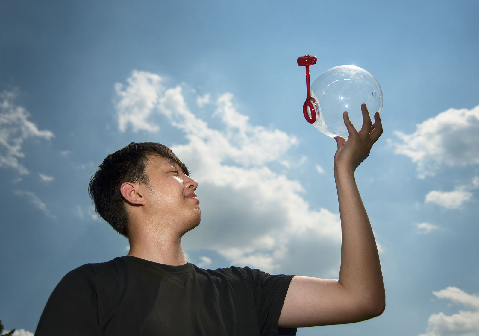 Designer Eric Ku with a soap bubble prototype created during GlassLab on Governors Island