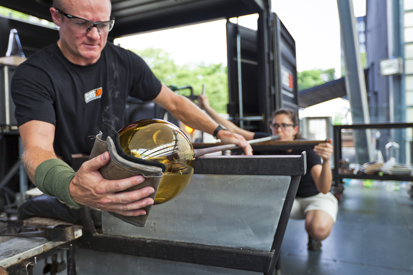 Glassmakers G Brian Juk and Annette Sheppard work with designer Jon Otis at GlassLab in Corning, July 2012