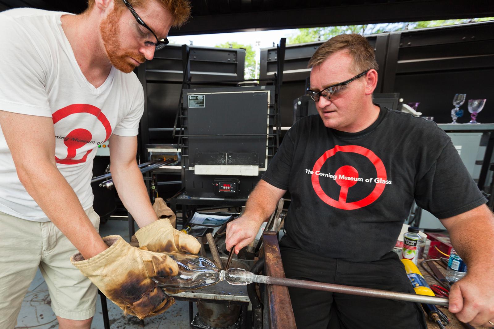 Gaffers George Kennard and Dane Jack work with designer Tom Scott at GlassLab in Corning