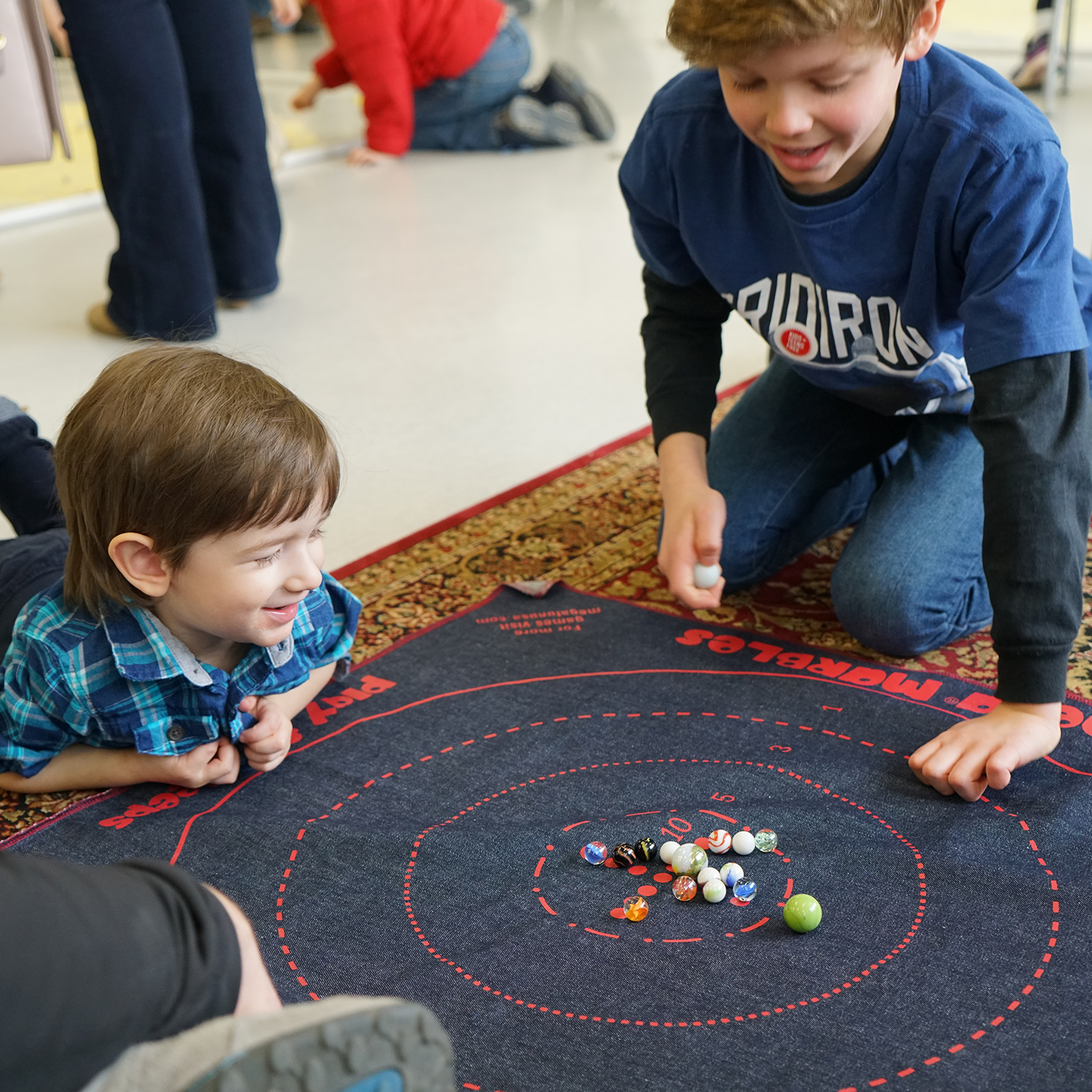 Two small boys playing marbles on the floor