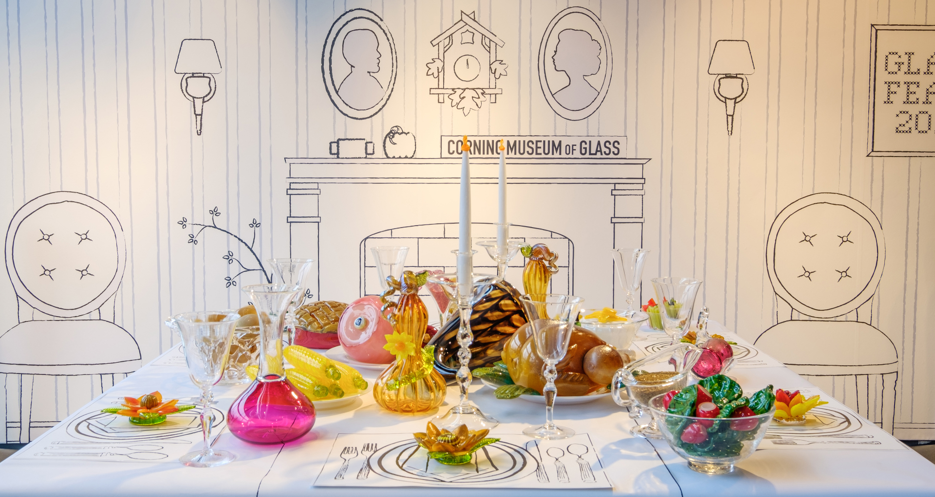 Turkey, smoked ham, and a cornucopia, all made out of glass, is set on a white tablecloth
