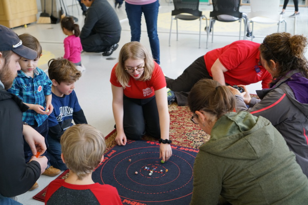 A teen volunteer at The Corning Museum of Glass leads a group children and adults in a game of marbles.