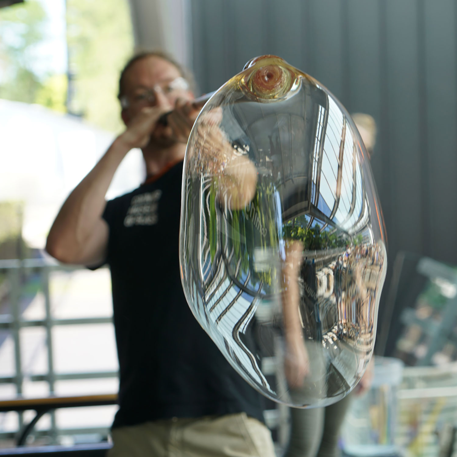 A man blows a large bubble of clear glass through a blowpipe.