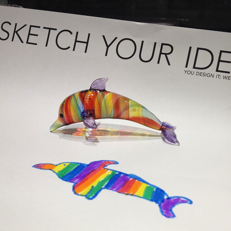 A sheet of paper says Sketch Your Idea and has a drawing of a rainbow-colored dolphin. On top of the paper is a glass rainbow-colored dolphin.