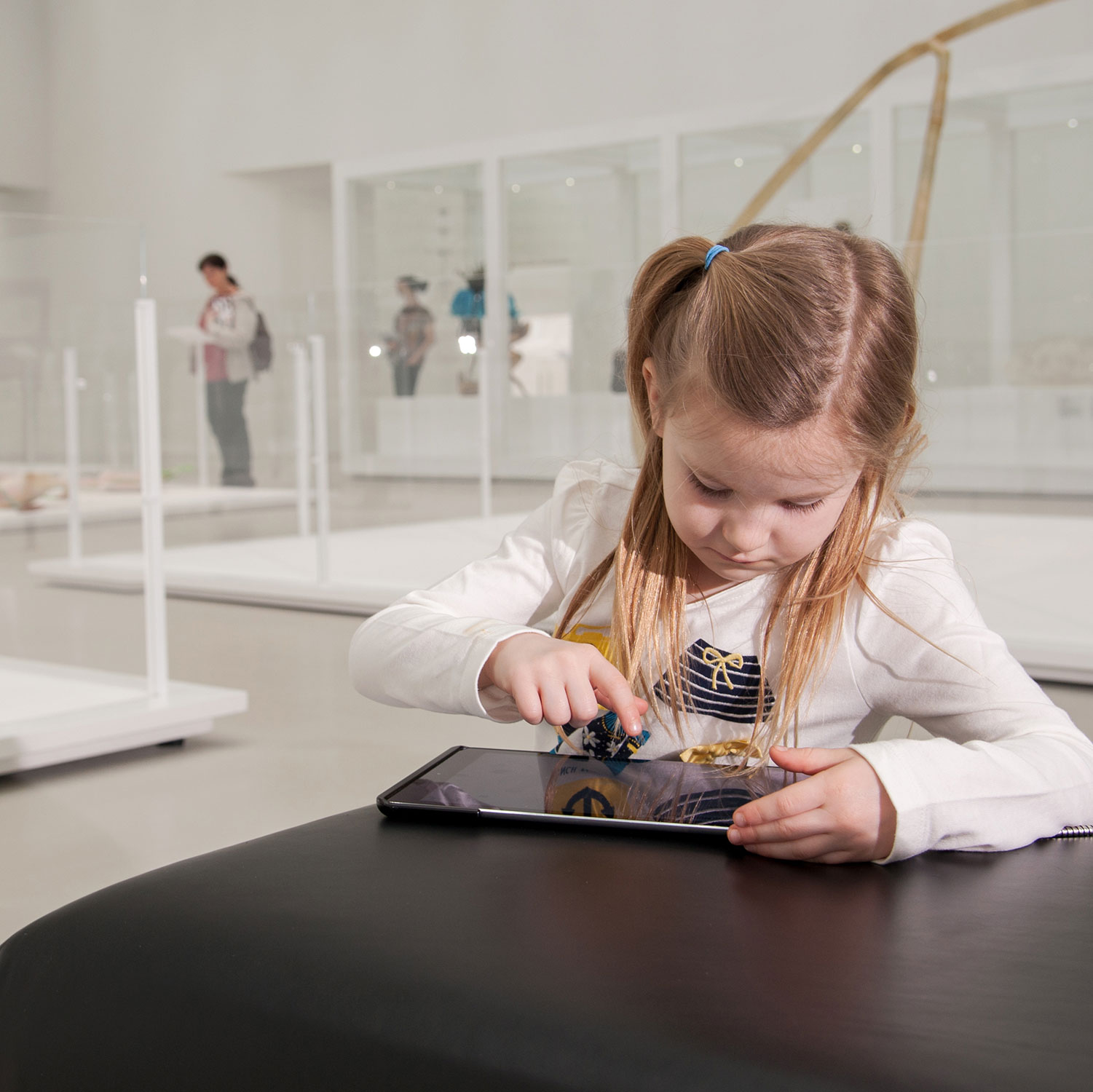 A young girl plays on a tablet in an art gallery.