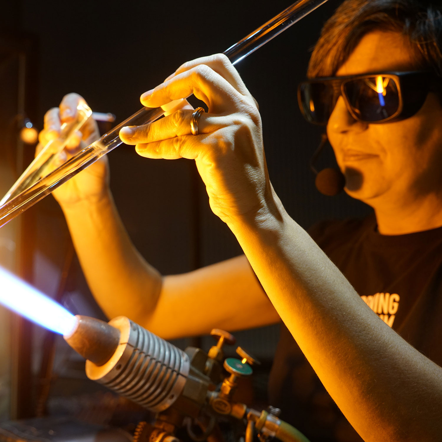 Woman wearing dark glasses works at a flameworking torch.