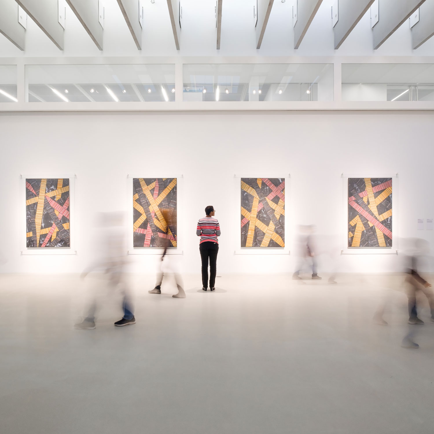 A person looks at panels of art glass hanging in a gallery.