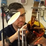 Matteo Seguso engrave a cylindrical vase, using two hands to hold the glass object