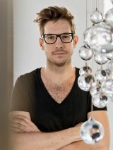 Man with short brown tousseled hair and black-framed glasses wears a black v-neck t-shirt and stands with his arms crossed. Slightly in front of him and to his left are a bunch of clear glass balls hanging from wires.