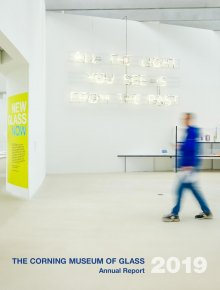 "In the foreground is a blurred view of a visitor in a blue jacket, jeans, and sneakers in motion walking through a gallery from the right. The background is light gray concrete floor with white walls/ On the left is the entrance to another gallery and a yellow wall sign with blue and turquoise lettering for the New Glass Now exhibition. In the center is a white neon wall sculpture saying: ""All the light you see is from the past."" On the right is a shelf with various small glass sculptures."