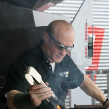Man with short cropped hair and sunglasses uses jacks to work a piece of hot blue glass.