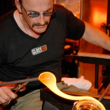A man with a mustache wearing dark glasses works with molten glass on the end of a punty.