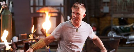Janusz Poźniak on the set of Blown Away holding a glob of molten glass on the end of a blow pipe.
