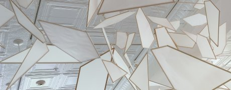 White angular shapes hang from a white ceiling in this artwork installation