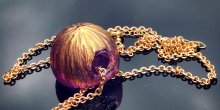 Spherical pink and gold glass bead pendant on a gold chain.