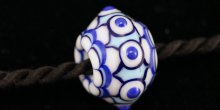 A close up view of a white glass bead with blue and white dots, creating an intricate pattern