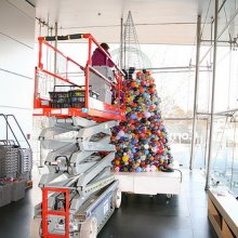 The giant glass ornament tree goes up in the Admissions Lobby