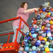 Suzette Lutchner Making Finishing Touches on the Giant Glass Ornamanet Tree