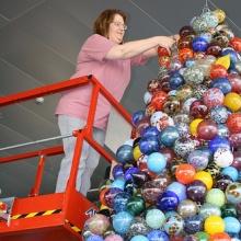 Suzette Lutchner Making Finishing Touches on the Giant Glass Ornamanet Tree