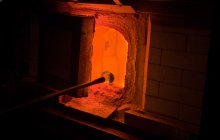 A punty with a blob of molten glass rests on the edge of furnace