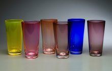 six transparent colored glass tumblers.