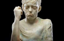 cast glass sculpture of a boy holding up his hands with his eyes closed