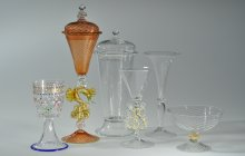 Six pieces of Venetian-style glassware. From left to right: a clear cup with flower dots, an orange goblet with a yellow dragon in the stem, three clear glass goblets in varying sizes, and a small clear and white striped bowl