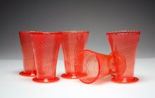 Group of five red glass beakers