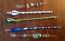 Five colorful glass icicle ornaments.
