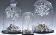 Three flamworked borosilicate organic sculptures under clear glass domes by Stephen Brucker