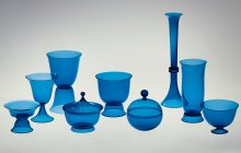 Tableware Set of Nine Blown Vessels, 1916. Designed by Josef Hoffmann (Austrian, 1870–1956); manufactured by Wiener Werkstätte and probably Meyr's Neffe. Mold-blown and hot-worked glass. Smallest object: H. 8.2 cm, Diam. 11.6 cm; Tallest object: H. 32.8 cm, Diam. 9.5 cm. The Corning Museum of Glass (74.3.24).