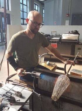 Artist Chris Giordano uses a torch to heat a white and clear glass sculpture on the end of a punty