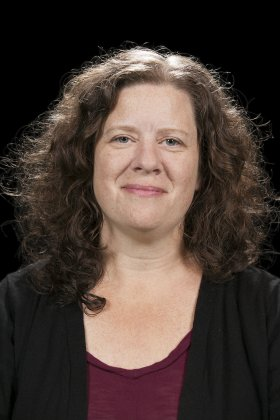 Headshot of Regan Brumagen smiling in front of a black background