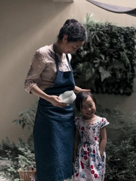 Dr. Xue stands with an apron on and a vessel in one hand while the other hand rests on the head of a child. Potted plants pepper the background.