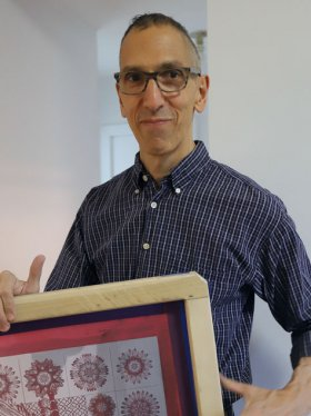 Man with close-cropped gray hair and glasses wearing a blue plaid shirt is holding a wood frame with a red print in it.