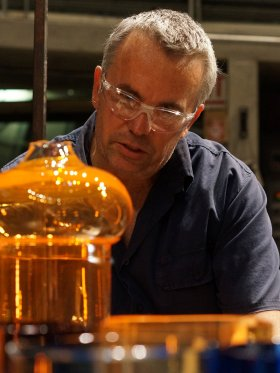 Man with short gray-ish hair wearing safety glasses and a blue shirt is focused on an orange piece of glass in front of him.