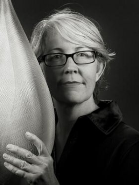 Black and white photo of a blonde woman wearing glasses with black frames. She is holding a large glass object next to the right side of her face.