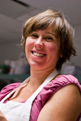 Woman with short brown hair wearing a work apron over a pink shirt smiles at the camera.