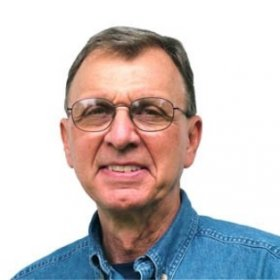 a man in glasses smiles at the camera while wearing a denim shirt