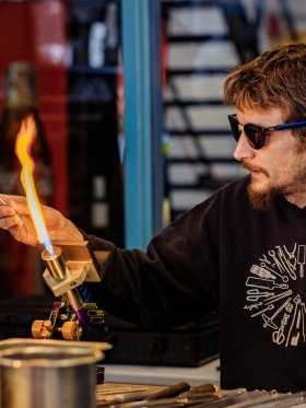 Artist Miles Parker uses a torch to melt a rod of clear glass