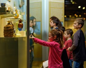 A group of children of various ages standing and pointing at a vase with a woven cover in the 35 Centuries of Glass gallery.
