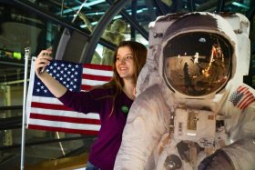 A Museum visitor smiles as she takes a selfie with a Buzz Aldrin cutout.