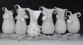 A series of white pitchers decorated with colorless glass flowers by Sandy Dukeshire