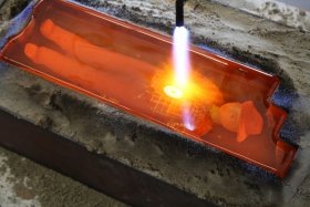 """""""Trenchard torching a 12 x 4 x 4.5"""" hot sand casting with handprinted & sculpted glass cowboy"""" by Stephanie Trenchard"""