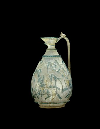 The Corning Ewer, Islamic, possibly Western Asia, possibly Egypt, about 1000.   Translucent pale green and colorless glass; blown, cased, relief-cut, drilled, handle applied H. 16 cm. Collection of The Corning museum of glass, purchased with funds from the Clara S. Peck Endowment (85.1.1)