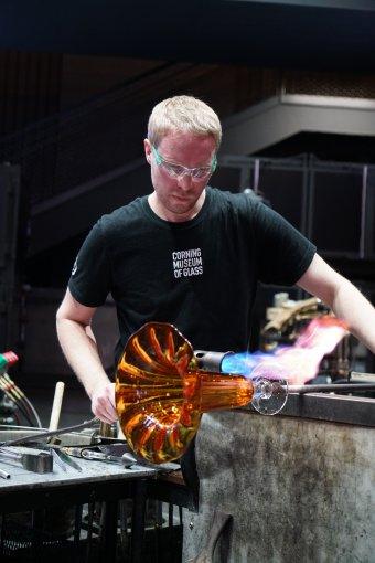 A glassblower heats a vase using a handheld torch.