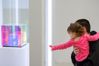 A toddler points at multicolored glass cube.