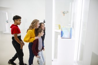 A group of children at various ages smile as they look a glass cube in a white walled room.