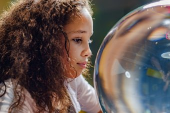 A child smiles softly as she gazes into a large glass orb.