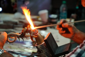 A small sculpture of a dragon is created over a concentrated flame.